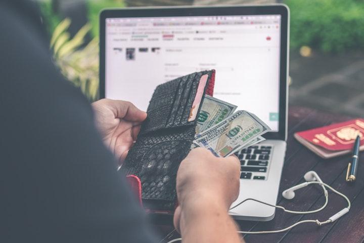 Plånbok med pengar och laptop
